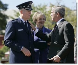 During the Armed Forces Farewell Tribute in Honor of General Richard B. Myers and Armed Forces Hail in Honor of General Peter Pace at Fort Myer's Summerall Field in Ft. Myer, Va., Friday, Sept. 30, 2005, President George W. Bush thanks General Richard B. Myers, with wife Mary Jo Myers, for his service as Chairman of the Joint Chiefs of Staff. White House photo by Paul Morse
