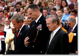 President George W. Bush, Major General James T. Jackson and Secretary of Defense Donald H. Rumsfeld (right) observe a 30-second moment of silence after a wreath-laying ceremony at the Tomb of the Unknown Soldier at Arlington National Cemetery on Memorial Day. Monday, May 26, 2003.  White House photo by Tina Hager