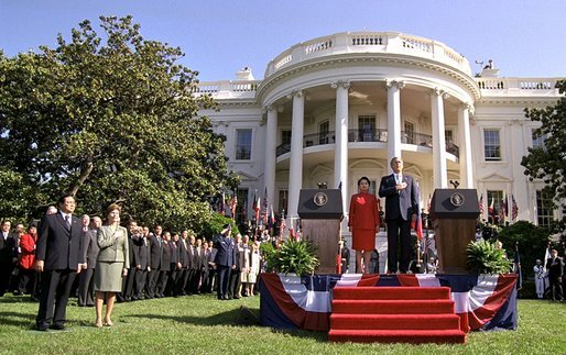 President Bush, President Arroyo, Mrs. Bush and Mr. Arroyo (far left) stand for the playing of the national anthems of the United States and the Philippines at the beginning of the ceremony. White House photo by Eric Draper