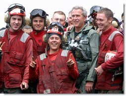 President George W. Bush poses with flight deck crew of the USS Abraham Lincoln May 1, 2003. White House photo by Paul Morse
