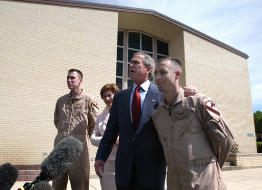 President George W. Bush puts his arm around Chief Warrant Officer David S. Williams as he speaks to the media with Chief Warrant Officer Ronald D. Young Jr., left, and Mrs. Bush after attending Easter church services at the 4th Infantry Division Memorial Chapel at Fort Hood, Sunday, April 20, 2003. Williams and Young are former POW's. White House photo by Eric Draper.