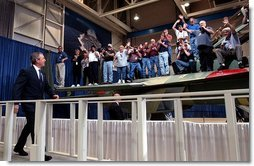 President George W. Bush walks to the stage as workers cheer during his introduction at the Boeing F-18 Production Facility in St. Louis, Mo., Wednesday, April 16, 2003.  White House photo by Eric Draper