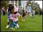 A helping hand is given during the Easter egg roll where little competitors use a spoon to carry a hard-boiled egg through the South Lawn race course and across the finish line at the White House Easter Egg Roll Monday, April 21, 2003. White House photo by Susan Sterner