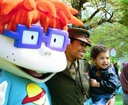 """A United States Marine and her son stand for pictures with Chuckie, a character from the cartoon, """"Rugrats,"""" during the White House Easter Egg Roll Monday, April 21, 2003. More than 30 children's characters wandered through the South Lawn during the day's festivities, including Clifford the Big Red Dog, Winnie the Pooh and the Berenstain Bears."""