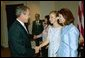 President George W. Bush greets Elizabeth Smart, center, and her mother Lois Smart in the Roosevelt Room Wednesday, April 30, 2003. President Bush met with the Smart family before the signing of the S. 151, PROTECT Act of 2003. White House photo by Eric Draper