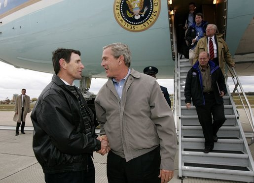 President George W. Bush meets USA Freedom Corps Greeter Jeff Kemp at Outagamie County Regional Airport in Appleton, Wisconsin, Friday, Oct. 15, 2004. For the past 12 years, Jeff has volunteered in the Oshkosh and Omro school districts. Once per week, he visits elementary school classrooms and reads to students. White House Photo by Eric Draper.