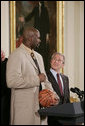 """President George W. Bush looks up as he prepares to receive an autographed ball from Shaquille O'Neal Tuesday, Feb. 27, 2007, as the 2006 NBA champions visited the White House. The President told the East Room audience he was most impressed by the Heat's work in their Miami community and added, """"I mean, I'm in awe of their athletic skills. Standing next to Shaq is an awe-inspiring experience."""" White House photo by Paul Morse"""