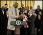 """President George W. Bush receives an autographed ball from Shaquille O'Neal Tuesday, Feb. 27, 2007, as the 2006 NBA champions visited the White House. The President told the East Room audience he was most impressed by the Heat's work in their Miami community and added, """"I mean, I'm in awe of their athletic skills. Standing next to Shaq is an awe-inspiring experience."""" White House photo by Eric Draper"""