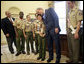 President George W. Bush hugs Cub Scout Bryson Hicks, 10, of San Diego, Calif., as he is given a statue of a Cub Scout in the Oval Office Monday, Feb. 26, 2007. In 2005 Bryson rescued his 4-year-old cousin, who waded into a lake after a remote control boat. Byrson used skills he learned in Scouting to save save his cousin. The scouts presented the President with the Boy Scouts of America's Report to the Nation, highlighting the organization's accomplishments during the past year. White House photo by Eric Draper