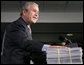 """President George W. Bush places his hand on a large stack of legislative earmarks as he addresses the employees at Micron Technology Virginia in Manassas, Va., Tuesday, Feb. 6, 2007, on the economy and fiscal responsibility. President Bush voiced his concern about earmarks being slipped into spending bills saying, """"If Congress is genuinely concerned about spending your money wisely, and I believe most members are, then, they must do something about earmarks."""" White House photo by Paul Morse"""
