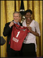 Ogonna Nnamani presents President George W. Bush with a team jersey from the Stanford University Women's volleyball team during a ceremony celebrating the 2005 NCAA champions in the East Room Friday, May 13, 2005. White House photo by Eric Draper