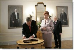 President George W. Bush signs a guest book after Latvian President Vaira Vike-Freiberga presented him the Order of the Three Stars, First-Class at Riga Castle in Riga, Latvia, Saturday, May 7, 2005. Established in 1924 to commemorate the founding of the Latvian State, the medal is awarded to recognize outstanding civil merit in the service of Latvia. White House photo by Eric Draper