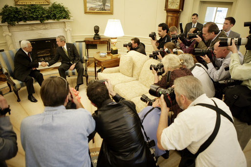 President George W. Bush shakes hands with President Mahmoud Abbas of the Palestinian Authority Thursday, May 26, 2005, as the press records the moment in the Oval Office of the White House. White House photo by Eric Draper