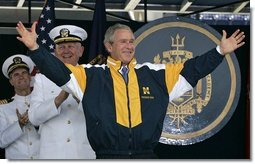 President George W. Bush tries on a Navy jacket during U.S. Naval Academy graduation ceremony in Annapolis, Md., Friday, May 27, 2005.  White House photo by Paul Morse