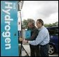 With the help of Rick Scott, Operations and Safety Coordinator, Shell Hydrogen, L.L.C., President George W. Bush replaces a nozzle on a hydrogen fueling pump at a Shell station in Washington D.C. The President visited the station, the first integrated gasoline/hydrogen station in North America, Wednesday, May 25, 2005, for a demonstration of its functions. White House photo by Paul Morse