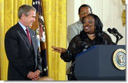 President George W. Bush receives praise from Welfare to Work graduate Ann Briscoe and her husband Alfred at an East Room event at the White House on June 4, 2002. White House photo by Paul Morse.