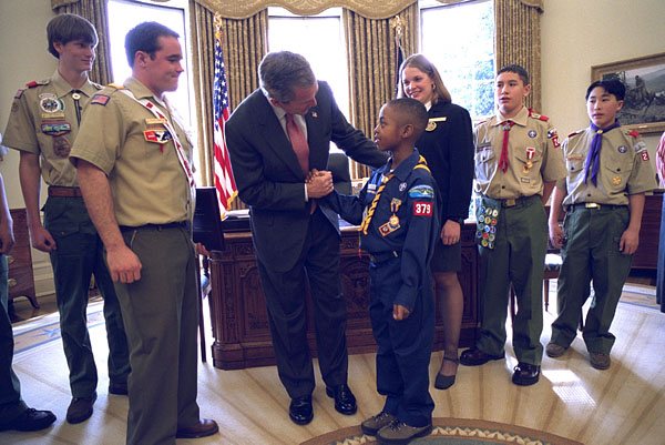 President George W. Bush talks with Jordon Wade, 9, of Pittsburgh during the presentation of the annual report by the Boy Scouts of America in the Oval Office Feb. 12, 2002. Other scouts included in the ceremony are, from left to right, Joe Honious, 16, of Dayton, Ohio; Clay Capp, 18, of Nashville, Tenn.; national Venturing President Marissa Morgan, 19, of Winston-Salem, NC; Joshua Cudd, 12, of Conroe, Texas; and Ryan Iwata, 12, of San Francisco. Not pictured is David Richey, 18, of Seattle, Wash. White House photo Eric Draper.