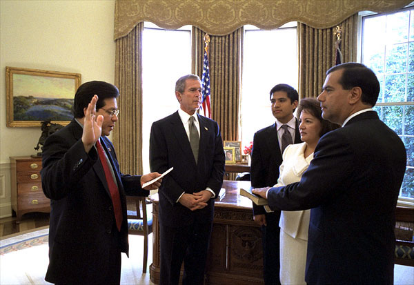 President George W. Bush watches as White House Counsel Albert Gonzales swears in Gaddi H. Vasquez as the 16th Peace Corps director in the Oval Office Feb. 14. Standing with Mr. Vasquez is his wife, Elaine, and son, Jason. White House photo by Eric Draper.