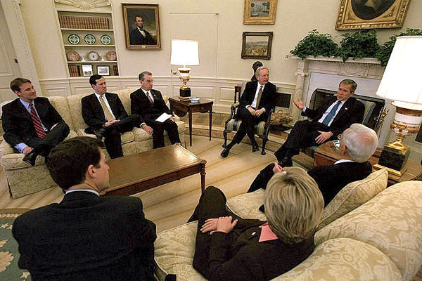 """President George W. Bush and Sen. Joseph Leiberman join other visiting Senators in the Oval Office to discuss Armies of Compassion, a faith-based initiative from the United States Senate. """"This legislation will not only provide a way for government to encourage faith-based programs to exist without breaching the separation of church and state, it will also encourage charitable giving as well,"""" explained President Bush. White House photo by Tina Hager."""