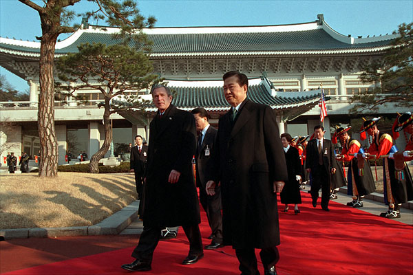 President George W. Bush and President Kim Dae-Jung proceed through an arrival ceremony at The Blue House in Seoul, Republic of Korea, Feb. 20, 2002.