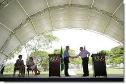 President George W. Bush and Brazil President Luiz Inacio Lula da Silva exchange handshakes Saturday, Nov. 6, 2005, after they delivered joint statements at the Brazil President's home, Granja do Torto. White House photo by Paul Morse
