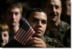 An unidentified member of the U.S. Armed Forces holds an American flag as he listens to the President's remarks on the War on Terror, Monday Nov. 14, 2005, at Anchorage's Elmendorf Air Force Base. The stop marked the first on a seven-day trip to Asia by the President and Mrs. Bush.  White House photo by Eric Draper