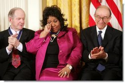 Queen of Soul Aretha Franklin wipes a tear after being honored with the Presidential Medal of Freedom Wednesday, Nov. 9, 2005, during ceremonies at the White House. Looking on are fellow recipients Robert Conquest, left, and Alan Greenspan.  White House photo by Paul Morse