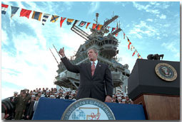"""President George W. Bush salutes during his remarks at the USS Enterprise Dec. 7. """"I'm grateful for this warm welcome on the deck of the """"Big E,"""" said the President. """"America is proud of this fine carrier and we're really proud of her crew. You're serving at a crucial moment for the cause of peace and freedom, and your country thanks you.""""White House photo by Paul Morse."""
