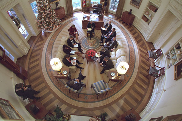 President George W. Bush hosts a meeting in the Oval Office decorated with the new presidential rug on December 20, 2001. The rug, which is unique to the Bush administration, arrived earlier in the week and was unveiled to the media on Friday December 21, 2001. Members from the Office of Homeland Security and other White House staff attended the meeting. The participants included (clockwise from the bottom), President George W. Bush, Governor Tom Ridge, Dr. Condoleezza Rice, Admiral Steve Abbot, Karen Hughes, Dean McGrath, Karl Rove, Albert Hawkins, Mitch Daniels, Josh Bolten, and Andy Card. White House Photographer Paul Morse is at left. White House photo by Paul Morse.