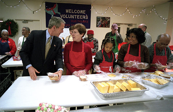 "Visiting ""Martha's Table"" center for homeless adults and children, President George W. Bush talks with volunteer Connie Jeremiah December 20. The president helped pack sandwiches into carrying crates at the center which has been providing food to the hungry since 1980. White House photo by Eric Draper."