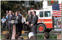 Accompanied by firemen and other distinguished guests, President George W. Bush speaks during a ceremony held to honor the gift of a new firetruck for the city of New York on the South Lawn Dec. 19. Donated by the state of Louisiana, the