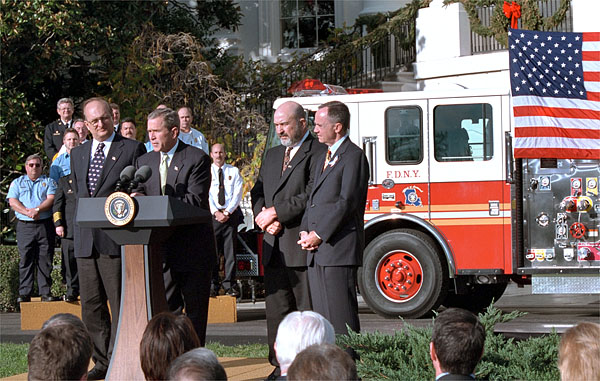 "Accompanied by firemen and other distinguished guests, President George W. Bush speaks during a ceremony held to honor the gift of a new firetruck for the city of New York on the South Lawn Dec. 19. Donated by the state of Louisiana, the ""Spirit of Louisiana,"" will replace one of the 35 firetrucks that were destroyed in the Sept. 11 attacks. Standing with the President is Ronald Goldman (left), Louisiana Governor Mike Foster (center), and Louisiana Representative Hunt Downer. White House photo by Tina Hager."