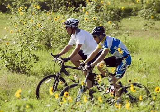 President George W. Bush and 2005 Tour de France winner Lance Armstrong take a ride together through a field of sunflowers on the President's ranch in Crawford, Texas on August 20, 2005. White House photo by Paul Morse