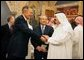 Former President George H.W. Bush, left, shake hands with newly crowned King Abdullah, right, during a retreat at King Abdullah's Farm in Riyadh, Saudi Arabia Friday, August 5, 2005, following the death of his half-brother King Fahd who passed away August 1, 2005. Interpreter Gamal Helal, center, is also pictured. White House photo by David Bohrer
