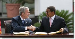 """President George W. Bush and President Jakaya Kikwete of Tanzania, shake hands after signing the $698 million Millennium Challenge Compact Sunday, Feb. 17, 2008, in Dar es Salaam. In signing the compact, President Bush said, """"We are partners in democracy. We believe that governments ought to respond to the people. We're also partners in fighting disease, extending opportunity and working for peace. Mr. President, I mentioned I was proud to sign, along with the President, the largest Millennium Challenge Account in the history of the United States here in Tanzania. It will provide nearly $700 million over five years to improve Tanzania's transportation network, secure reliable supplies of energy, and expand access to clean and safe water."""" White House photo by Chris Greenberg"""