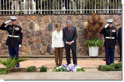 Flanked by saluting U.S. Marines President George W. Bush and Mrs. Laura Bush pause for a moment of silence after laying a wreath on a mass grave at the genocide memorial Tuesday, Feb. 19, 2008, at the Kigali Memorial Centre in Kigali, Rwanda. White House photo by Eric Draper