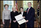 President George W. Bush and Mrs. Bush present the Preserve America award for heritage tourism to Dr. Bonnie McEwan, Executive Director, Mission San Luis of Tallahassee, Fla., left, and Mrs. Columba Bush, the First Lady of Florida, in the Oval Office Monday, May 1, 2006. White House photo by Eric Draper