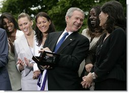 President George W. Bush laughs with members of the Sacramento Monarchs as he tries on their 2005 Women's National Basketball Association Championship ring during a congratulatory ceremony held in the East Garden at the White House Tuesday, May 16, 2006.  White House photo by Eric Draper