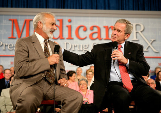 President George W. Bush speaks with retired senior Peter Navarro during A Conversation on the Medicare Prescription Drug Benefit at the Asociacion Borinquena de Florida Central, Inc., in Orlando Wednesday, May 10, 2006. White House photo by Eric Draper
