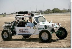 President George W. Bush rides in a U.S. Border Patrol dune buggy during a tour of the Yuma sector near the U.S. Mexico border in Yuma, Arizona, Thursday, May 18, 2006. White House photo by Eric Draper
