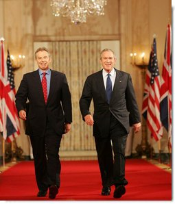 """President George W. Bush and Prime Minister Tony Blair of Great Britain, walk through Cross Hall en route to the East Room Thursday night, May 25, 2006, for a joint press availability during which the President said of Iraq's new government, """"The United States and Great Britain will work together to help this new democracy succeed."""" White House photo by Shealah Craighead"""