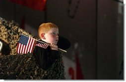 Keeping a grip on his souvenir flags, a boy listens to President George W. Bush at Pease Air National Guard Base in Portsmouth, N.H., Thursday, Oct. 9, 2003. White House photo by Tina Hager.