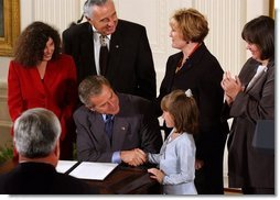 After signing a proclamation recognizing October as Domestic Violence Month, President George W. Bush shakes hands with Monique Blais, 7, the young artist who designed the Stop the Violence postage stamp in the East Room Wednesday, Oct. 8, 2003.  White House photo by Tina Hager