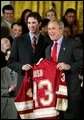 President George W. Bush stands with Ryan Caldwell of the University of Denver men's hockey team during a ceremony in the East Room congratulating four NCAA teams for winning national titles Wednesday, May 19, 2004. White House photo by Paul Morse.