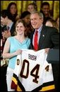 President George W. Bush stands with Kelsey Bills of the University of Minnesota's women's hockey team during a ceremony in the East Room congratulating four NCAA teams for winning national titles Wednesday, May 19, 2004. White House photo by Paul Morse.
