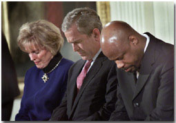 """President George W. Bush lowers his head in prayer between Shirley Dobson, left, and Rev Wintley Phipps during a reading of """"Our Nations Prayer"""" at the White House reception for the 50th Anniversary of the National Day of Prayer. WHITE HOUSE PHOTO BY ERIC DRAPER"""