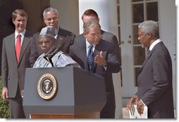 President George W. Bush welcomes UN Secretary General Kofi Annan to the podium after his announcement of Presidential HIV/AIDS Trust Fund Initiative as Nigerian President Olusegun Obsanjo looks on at left in the Rose Garden, Friday, May 11.  White House photo by Eric Draper