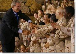 President George W. Bush greets troops during his introduction at Camp As Sayliyah in Doha, Qatar, Thursday, June 5, 2003.   White House photo by Paul Morse