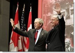 "President George W. Bush and Prime Minister Paul Martin wave after their remarks at Pier 21, Canada's historic point of immigration in Halifax, Canada, Dec. 1, 2004. During his remarks, President Bush thanked Canada for the hospitality to more than 33,000 passengers whose airplanes were diverted because of the 911 attacks. ""You opened your homes and your churches to strangers. You brought food, you set up clinics, you arranged for calls to their loved ones, and you asked for nothing in return,"" said the President. White House photo by Paul Morse"