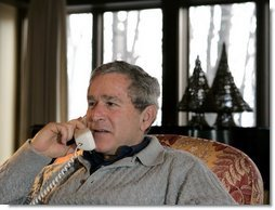 President George W. Bush participates in Christmas Eve Phone Calls to members of the armed forces at Camp David, Friday, Dec. 24, 2004.  White House photo by Eric Draper